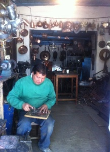 A shopkeeper on the road into town creating brass housewares by hand, as his father had done before him.