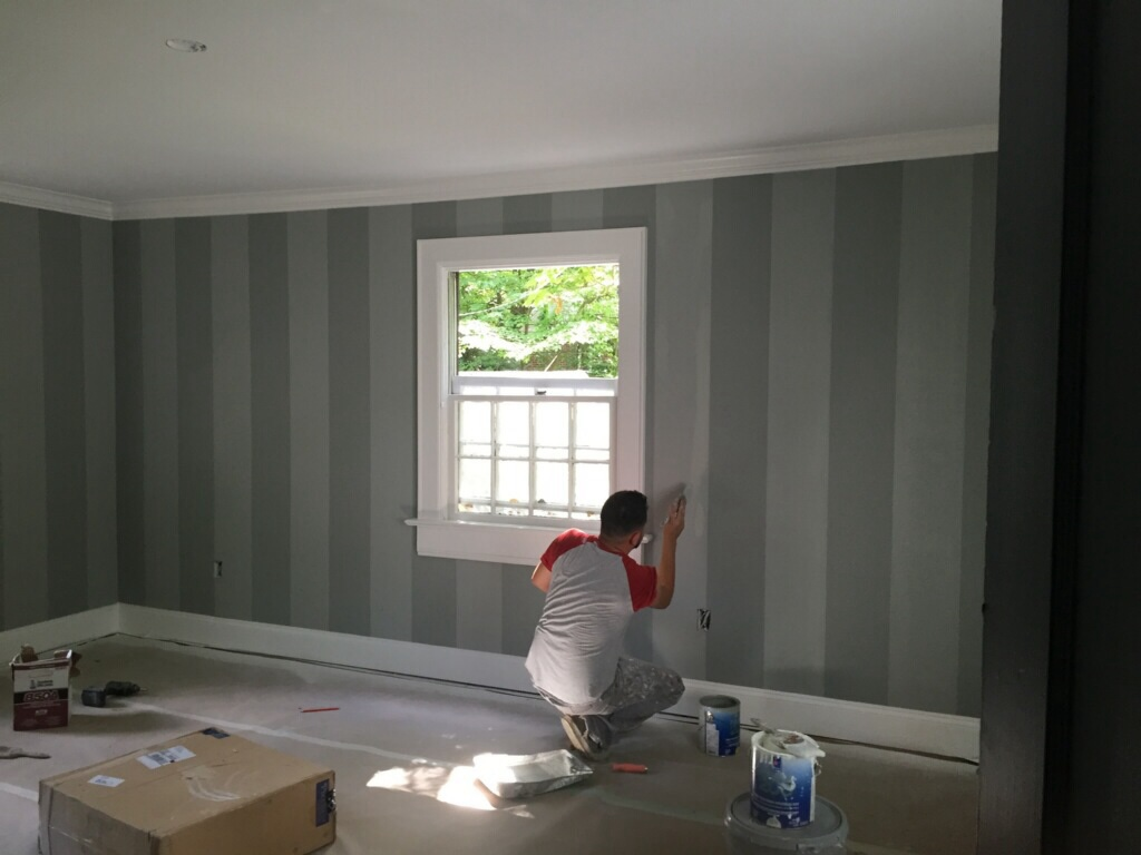 The painter puts the final touches on the striped paint in the master bedroom.